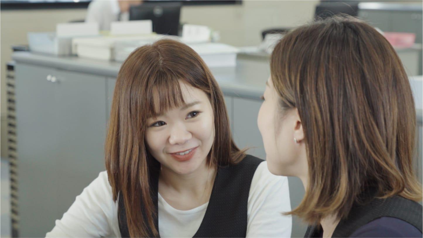 同僚と話し合っている様子の画像